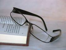 Vidrios que ponen en un libro Imágenes de archivo libres de regalías