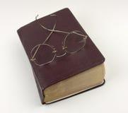 Vidrios que se sientan en un libro de Brown Imagenes de archivo