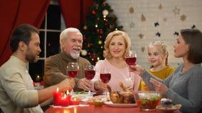 Vidrios que tintinean de la familia amistosa con el vino el víspera de Navidad, árbol que brilla detrás almacen de metraje de vídeo