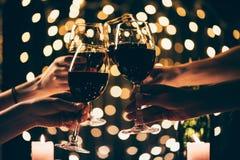 Vidrios que tintinean de la gente con el vino Imagenes de archivo