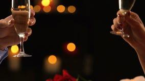 Vidrios que tintinean de la mujer y del hombre con el champán, fecha romántica, celebración del fest almacen de video