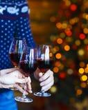 Vidrios que tintinean de vino rojo en manos en backgr de las luces de la Navidad Imagen de archivo libre de regalías