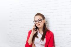 Vidrios rojos de la chaqueta de la empresaria del teléfono celular del desgaste serio de la llamada que hablan en móvil Fotos de archivo