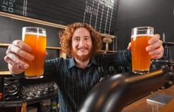Vidrios sonrientes felices de Hold Two Beer del camarero, soporte en el contador, camarero Serving Order Imágenes de archivo libres de regalías