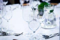 Vidrios transparentes en una tabla de banquete con las cucharas y las bifurcaciones Imagen de archivo libre de regalías