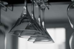 Vidrios vacíos colgantes de martini en el estante Foto de archivo