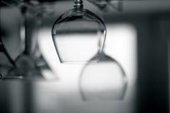 Vidrios vacíos colgantes en el estante Imagenes de archivo