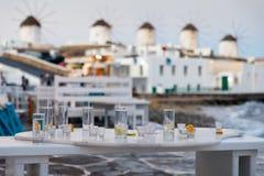 Vidrios vacíos de bebidas y cócteles delante de los molinoes de viento famosos de Mykonos Fotografía de archivo