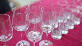 Vidrios vacíos del vino y de agua en un banquete metrajes