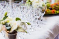 Vidrios vacíos en la tabla blanca, fila de A del vidrio vacío del champán Foto de archivo