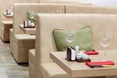 Vidrios vacíos en las tablas y los sofás de cuero beige Foto de archivo