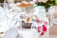 Vidrios vacíos múltiples en la tabla en atmósfera brillante foto de archivo libre de regalías