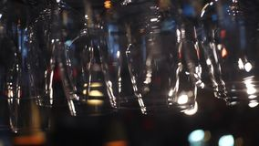 Vidrios vacíos para el vino y otras bebidas alcohólicas que cuelgan sobre el contador de la barra Cap?tulo Vista borrosa de copas almacen de video
