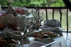 Vidrios vacíos y comida de la tabla festiva Fotos de archivo libres de regalías