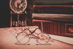 Vidrios viejos en voluta con los libros y el reloj viejo El vintage entonó la foto Imagen de archivo