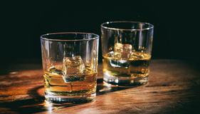 Vidrios whisky y cubos de hielo en contador de madera Fotos de archivo