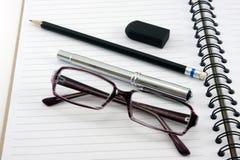 Vidrios y borrador del lápiz del cuaderno en el fondo blanco Fotos de archivo libres de regalías