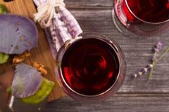 Vidrios y botella de vino rojo con queso de la uva, de la lavanda y del pesto en la tajadera Imagen de archivo libre de regalías
