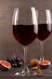 Vidrios y botella de vino rojo con queso de la uva, de la lavanda y del pesto en la tajadera Fotos de archivo