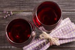 Vidrios y botella de vino rojo con queso de la uva, de la lavanda y del pesto en la tajadera Fotos de archivo libres de regalías