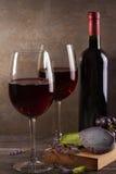 Vidrios y botella de vino rojo con queso de la uva, de la lavanda y del pesto en la tajadera Imagen de archivo