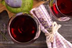 Vidrios y botella de vino rojo con queso de la uva, de la lavanda y del pesto en la tajadera Foto de archivo