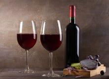Vidrios y botella de vino rojo con queso de la uva, de la lavanda y del pesto en la tajadera Imágenes de archivo libres de regalías