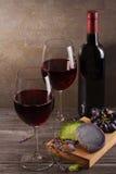 Vidrios y botella de vino rojo con queso de la uva, de la lavanda y del pesto en la tajadera Foto de archivo libre de regalías