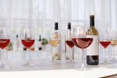 Vidrios y botellas con el vino delicioso en la tabla foto de archivo libre de regalías