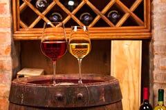Vidrios y botellas de vino blanco rojo y en barril viejo en bodega Fotografía de archivo