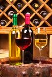 Vidrios y botellas de vino blanco rojo y en barril viejo en bodega Fotos de archivo libres de regalías