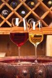 Vidrios y botellas de vino blanco rojo y en barril viejo en bodega Fotos de archivo