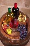 Vidrios y botellas de vino blanco rojo y en barril viejo en bodega Foto de archivo libre de regalías