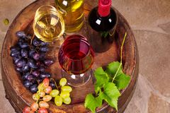 Vidrios y botellas de vino blanco rojo y en barril viejo en bodega Imagen de archivo libre de regalías