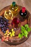 Vidrios y botellas de vino blanco rojo y en barril viejo en bodega Imágenes de archivo libres de regalías