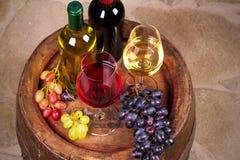 Vidrios y botellas de vino blanco rojo y en barril viejo en bodega Fotografía de archivo libre de regalías