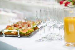 Vidrios y comida para comer con los dedos vacíos del champán en la tabla festiva de la boda Fotos de archivo