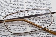 Vidrios y diccionario foto de archivo
