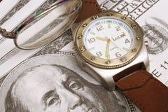 Vidrios y dinero de reloj Foto de archivo libre de regalías