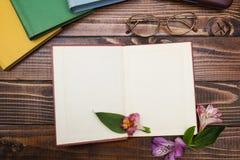 Vidrios y libro abierto con las flores en una tabla de madera marrón foto de archivo