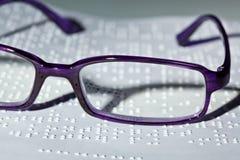 Vidrios y libro en Braille. Imagenes de archivo