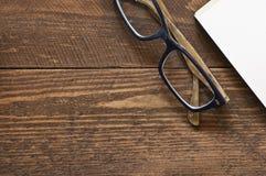 Vidrios y libro en la madera Foto de archivo libre de regalías