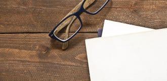 Vidrios y libro en la madera Imagenes de archivo