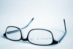 Vidrios y papel con E=mc2 Fotografía de archivo