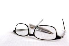 Vidrios y pluma en el papel Fotos de archivo libres de regalías