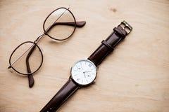 Vidrios y reloj en superficie de madera Fotografía de archivo libre de regalías