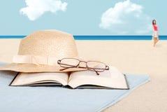 Vidrios y sombrero del libro en la playa Imagenes de archivo