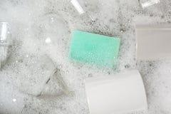 Vidrios y tazas en un fregadero por completo del agua jabonosa Fotografía de archivo libre de regalías