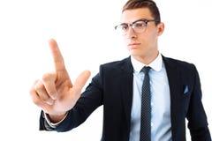 Vidrios y traje que llevan del hombre de negocios, tocando un scre imaginario fotografía de archivo