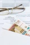 Vidrios y un sobre con las cuentas de la rublo que mienten en la hoja de la contabilidad de la hora laborable Foto de archivo libre de regalías